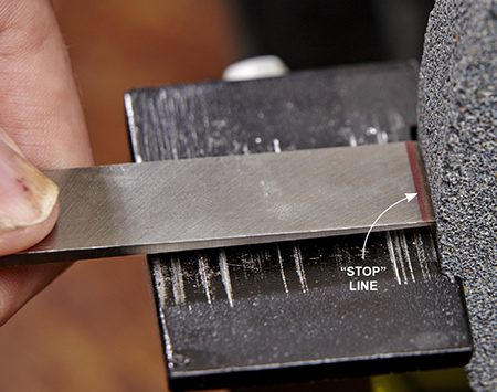 <b>Photo 10: Blunt the end</b></br> Slowly push the chisel into the coarse grinding wheel to remove any nicks. Creating a blunt end will further reduce the chances of overheating when you grind a new bevel.