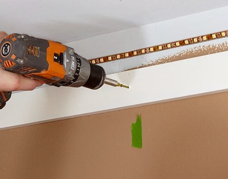 <b>Photo 2: Fasten the base</b></br> <p>Drive 2-in. screws through the base into each stud. Sink the screws flush and place them high enough to be covered by the crown molding.</p>
