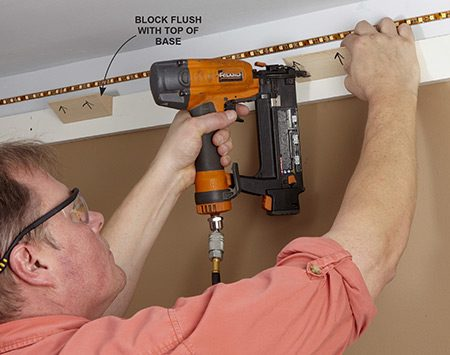 <b>Photo 3: Attach the support blocks</b></br> <p>Cut blocks to support the crown molding. Fasten them into place with 2-in. 18-gauge brads. Mark them so you don't confuse which way is up.</p>