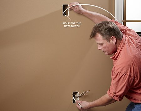 <b>Photo 5: Fish the cable</b></br> <p>Cut a hole in the wall for the switch box, and run a cable down through the outlet box hole below it.</p>