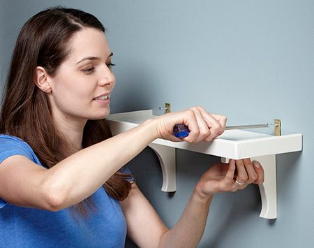 <b>Photo 7: Hang your shelf with small angle brackets</b></br> <p>For a light-duty shelf like this, you don't need to screw it to the studs. Just make sure the shelf is level and use drywall anchors in the wall.</p>