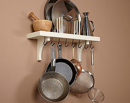 <b>Pothooks and lids</b></br> <p>This shelf has hooks screwed underneath to hold frying pans. We gave the hooks a dark finish by heating them with a torch. On our shelf, we cut off some of the threaded part of each hook with a bolt cutter because they were too long. The pot lids are held in place with two rows of 5/16-in. dowels. For heavier lids, use 3/8-in. dowels.</p>