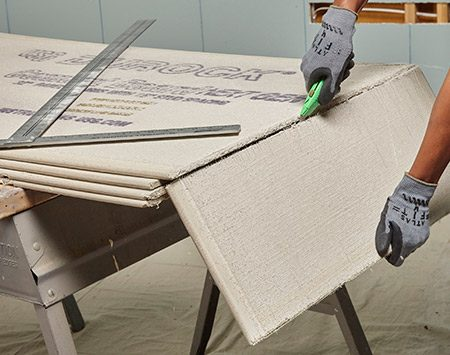 <b>Photo 2: Break the board</b></br> <p>Bend the cement board to snap it along the scored line. Then cut through the mesh on the back of the board with a utility knife. Use the utility knife to clean up the cut and create a straight edge.</p>