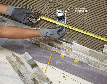<b>Photo 11: Measure for the outlet notch</b></br> <p>Measure from the closest installed stone and transfer these marks to the stone you need to notch. You can stick masking tape to the stone for easier marking.</p>