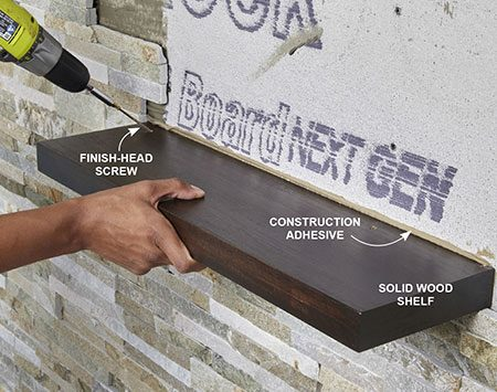 <b>Photo 14: Attach shelves with angles screws</b></br> <p>Apply construction adhesive to the back edge of the shelf and rest it on top of a stone. Press the shelf against the wall while driving angled finish-head screws through the shelf and into studs. Make sure to position the shelves over two studs.</p>
