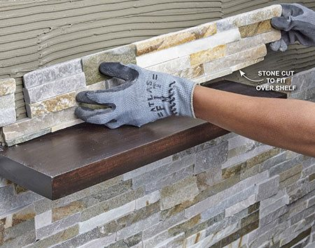 <b>Photo 15: Cut stone to fit over the shelf</b></br> <p>If your shelves are exactly as long as one piece of stone, you can simply cut off the thickness of the shelf from the length of one piece of stone. Otherwise, notch the stone to fit around the shelf.</p>