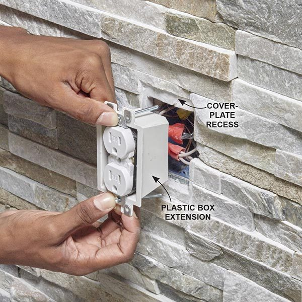 <b>Photo 18: Install the box extension</b></br> <p>Slip a plastic box extension over the outlet and slide it into the electrical box. Mount the outlet to the electrical box with the extra-long screws provided in the package.</p>