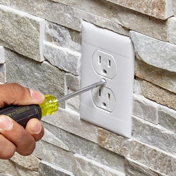 <b>Photo 19: Attach the cover plate</b></br> <p>Set the cover plate into place and make sure it's tight to the stone, without large gaps. If it's a good fit, screw it onto the outlet.</p>