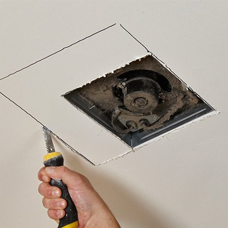 <b>Photo 2: Mark and cut the ceiling opening</b></br> Using the template provided, trace the new opening onto the ceiling. Then cut along the lines using a drywall saw. Cut shallower strokes around the flexible duct so you don't puncture it.