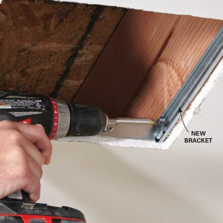 <b>Photo 4: Mount the bracket</b></br> Slide the bracket through the opening and extend it so it contacts the joists on each side of the opening. Secure both sides to the joists with drywall screws.
