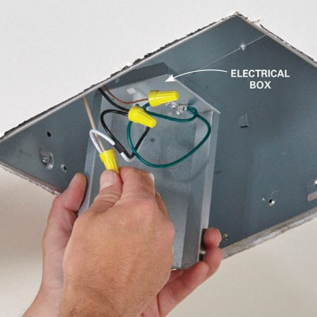 <b>Photo 6: Connect the wires</b></br> Secure the hot (black), neutral (white) and ground (green/bare copper) wires with wire nuts. Then slide the metal electrical box into place in the housing and attach it with the screw provided.