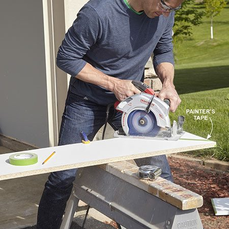 <b>Photo 1: Cutting melamine board</b></br> Cut one melamine board at a 45-degree angle and use it as a pattern to mark the others for cutting. Mark your cutting line on a strip of painter's tape—the tape reduces chipping as you cut.