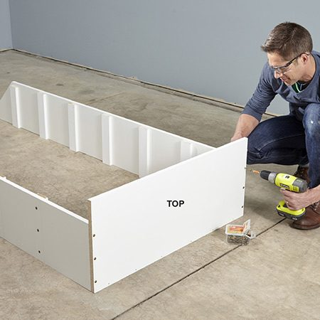 <b>Photo 4: Assemble the unit</b></br> Drill holes in the top, then drive cabinet screws to fasten the top to the sides.