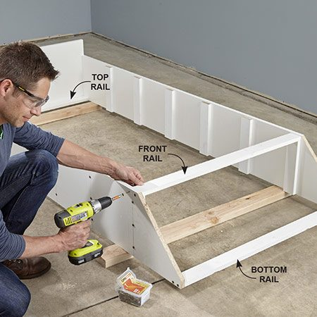 <b>Photo 5: Install the rails</b></br> Drill screw holes in the sides and fasten the three rails. You'll need to raise the unit off the floor in order to screw the top and bottom rails.