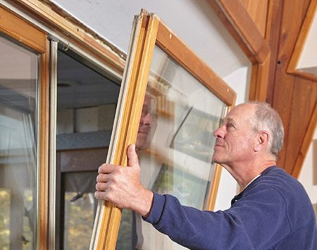 <b>Photo 2: Tilt and Lift</b></br> <p>Tilt the top of the sliding door out far enough to clear the frame. Then lift the door up and off the bottom track (get help—it's heavy). Set the door on a drop cloth and lean the door against a wall.</p>