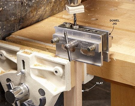 <b>Photo 7: Drill dowel holes</b></br> <p>Align the marks on the dowel jig with your marks on the bench part and lock the jig onto the part. It's best to drill the holes in two steps. Drill about halfway, remove the bit to clear out the wood chips and then finish the hole with a second plunge.</p>