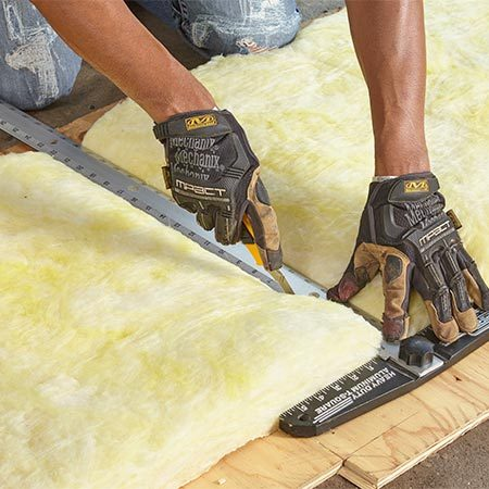 <b><b>Photo 2:</b> Cut the batting</b></br> <p>Roll out the batting with the vinyl side down and mark the cutting lines. Place the batting on scrap plywood. Then compress the insulation with a straightedge and cut with a utility knife.</p>