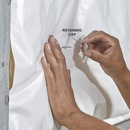 <b><b>Photo 3:</b> Lock the batting in place</b></br> <p>Line up the insulation so it's centered in the panel and push it against the retaining pin until it punctures the vinyl facing. Then push the retaining cap over the pin until it snaps into place.</p>