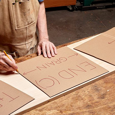<b><b>Photo 2:</b> Lay out parts with templates</b></br> <p>Your wall unit may require dozens of parts, but there are only three rough sizes. Cut full sheets of plywood into 16-in.-wide strips, then mark the parts using a set of three cardboard templates, based on the rough sizes given in the Cutting List.</p>