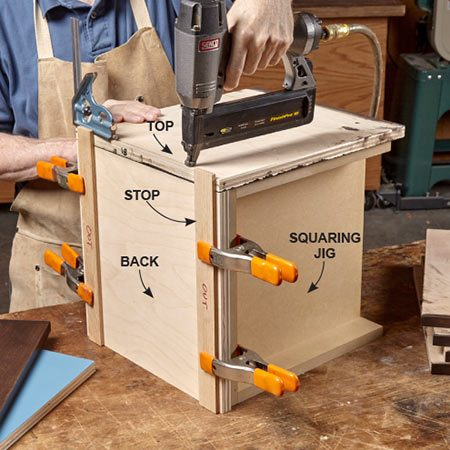 <b><b>Photo 8:</b> Join the top and bottom to the back</b></br> <p>Begin assembling each unit by fastening a top and bottom to a back. Use two simple jigs and a pair of stops to align the parts. Shoot three brads to lock the parts in place, then drill pilot holes and drive in screws.</p>