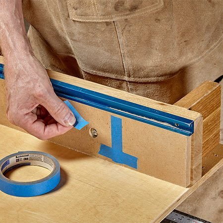 <p><b>Photo 3:</b> Adjust with tape</p> <p>To correct the angle, add tape to the sled's fence one piece at a time. Repeat the flip test and add or subtract tape until the gap disappears.</p>