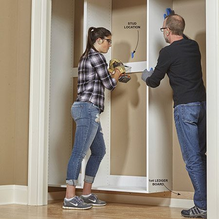 <b>A ledger board makes installation easy</b></br> <p>Once assembled, each cabinet box weighs about 100 lbs. To make hanging them easier, screw a 1x4 or 2x4—called a ledger board—to the back wall of the closet down near the floor. Make sure it's perfectly straight and level. Mark the stud locations with masking tape. Then get somebody to help you lift each box onto the ledger board, which will hold it in position until you can screw it to the wall. Drive 3-in. washer-head screws through the hanging strips of all three boxes and into the wall studs.</p>