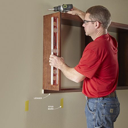 <b>Photo 9: Mount the center shelf</b></br> <p>Level the ledger (L) and attach it to the wall studs with trim screws. Rest the center shelf unit on the ledger, aligning the sides with the ends of the ledger. Make sure the sides are plumb. Then drive screws through the hanging cleat into the studs to hold the shelf in place. Drive trim-head screws down through the bottom shelf into the ledger.</p>