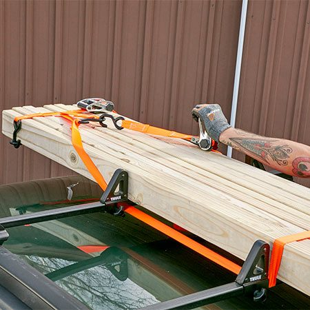 <b>Photo 2: Secure the load to the rack</b></br> <p>Hook a ratchet strap to the front bundle strap. Then wrap this strap around both crossbars and tighten. Repeat for the rear end of the bundle.</p>