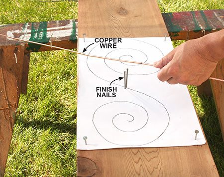 <b>Photo 3: Make a bending jig</b></br> <p>The bending jig for the wire scrolls is a piece of scrap wood with a copy of the scroll pattern tacked to it. Two finish nails in the middle hold the copper wire.</p>