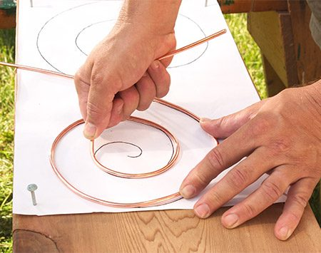 <b>Photo 4: Follow the pattern</b></br> <p>Bend the scrolls with your hands, following the pattern. The copper wire is soft and will bend easily. When you've bent one side, weight it down and bend the other.</p>