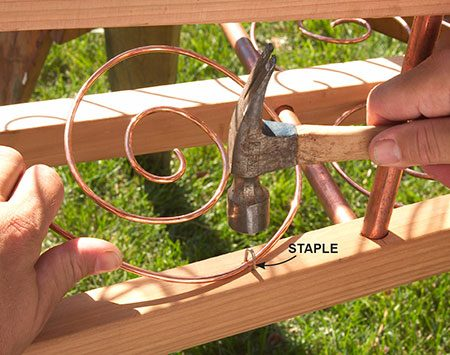 <b>Photo 5: Fasten the scrolls</b></br> <p>Attach the scrolls with small fence staples. You can bend the scroll out of the way temporarily to make room for the hammer.</p>