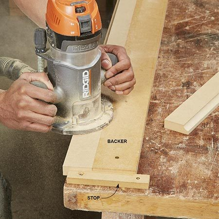 <b>Photo 4: Rout the long edges</b></br> Find a large, flat work surface that you can screw into. Attach a stop and a backer board to the work surface as shown above. Make sure the trim overhangs the work surface slightly to allow room for the router bit guide bearing.
