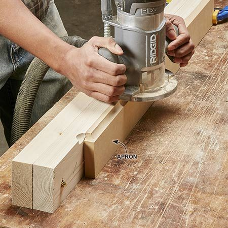 <b>Photo 6: Rout the aprons</b></br> Rip two lengths of 2x4 to the same width as the lower window apron (3 in.) and screw them together. Toe-screw the 2x4s to the work surface and clamp the lower window apron part to the 2x4s. Now you can easily shape both ends and the long edge with the router. The 2x4s provide the support needed to hold the router level as you rout the narrow ends.