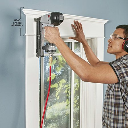 <b>Photo 11: Nail the head casing assembly into place</b></br> Center the head casing assembly over the window, making sure the fillet overhangs the side casings evenly. Then nail through the head casing assembly into the wall framing above the window.