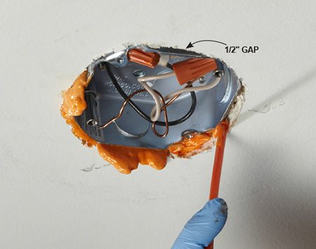 <b>Photo 1: Fill Ceiling Box Gaps with Fire-Blocking Foam</b></br> <p>Invert the spray foam can and shove the tube up into the gap. Gently squeeze the trigger and slowly pump foam into the gap. Let it cure for about two hours. Then cut off the excess and reinstall the light fixture.</p>