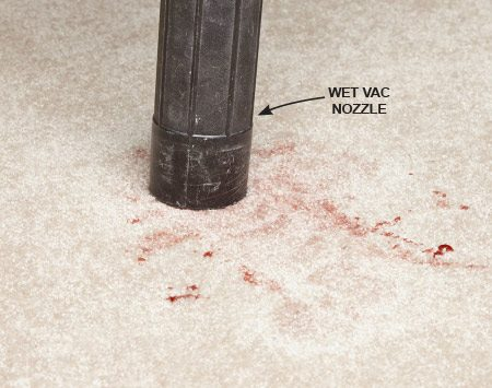 <b>Photo 1: Suck Up the Mess</b></br> Push the hose directly onto the carpet fibers and leave it in place for several seconds. Don't rub or drag the hose over the carpet. Move to an adjoining spot and repeat as many times as required to remove as much of the spill as possible.