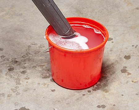 <b>Photo 4: Clean Your Shop Vacuum the Easy Way</b></br> Dump some disinfecting cleaner into a bucket of warm water and drop your hose into it. Empty the tank and rinse both the hose and tank with water.