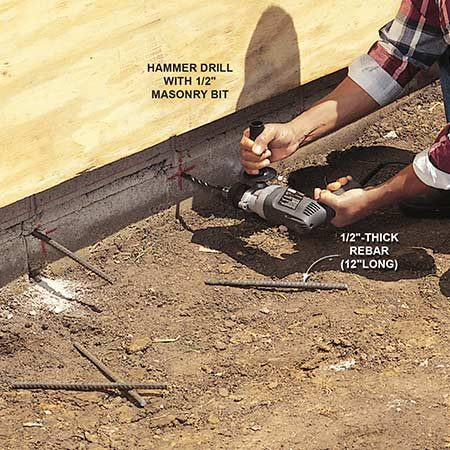 <b>Pin the pad to the foundation</b></br> Using a hammer drill and masonry bit, drill 1/2-in. holes 4 in. deep in your home's concrete foundation and space them about a foot apart. Then, using a hammer, tap 12-in.-long pieces of 1/2-in. rebar into the holes to connect the new pad to the foundation. The rebar will ensure that your new pad maintains its slope away from the house. <b>Note:</b> Not all municipalities allow this practice, so check with your local building inspector.