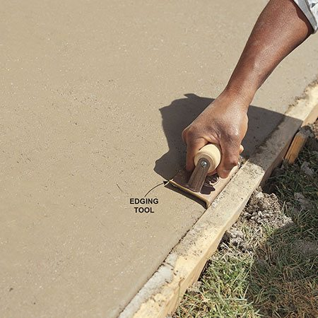 <b>Round over the edges</b></br> Fifteen to 30 minutes after screeding, use a steel edging tool—about $6 at home centers— to smooth and round over the edges of the pad. This gives a nice-looking shape to the edges and forces the aggregate away from the corner. Do this a few times during floating (see Photo 5) and after.