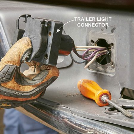 <b>Photo 1: Remove the trailer light connector</b></br> <p>Reach behind the bumper and hold each nut as you unscrew the trailer light screws. Place the small parts in a magnetic tray or zipper-top bag so you don't lose them.</p>