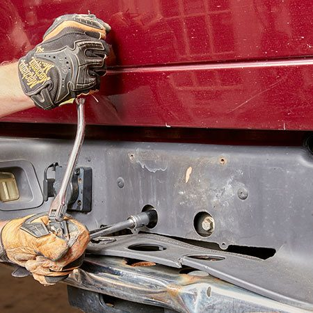 <b>Photo 3: Remove the smaller bolts</b></br> <p>Remove the license plate to reveal the bolts that hold the bumper to the trailer hitch. Use a socket and ratchet to remove them.</p>