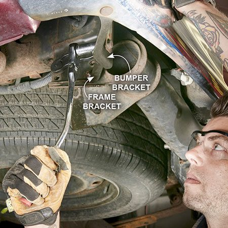 <b>Photo 4: Disconnect the bracket bolts</b></br> <p>Use a deep socket and ratchet to remove the bottom nut connecting the bumper bracket to the frame bracket. Repeat on both sides. Then loosen the top nuts on the same brackets, but don't remove them until you're out from under the vehicle.</p>