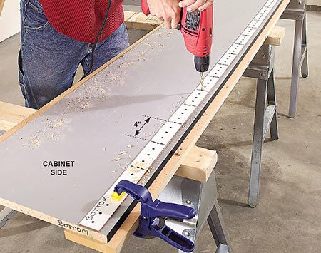 <b>Photo 4: Drill shelf support holes</b></br> <p>Drill 1/4-in. shelf support holes through cabinet sides using a scrap of pegboard as a guide. For end panels that won't support shelves on one side, place a stop collar on the drill bit.</p>