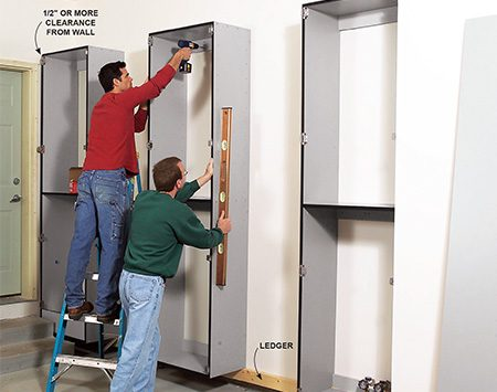 <b>Photo 11: Hang the cabinets</b></br> <p>Set the cabinet into place and screw it to the ledger. Then level the cabinet and fasten it to the wall with pairs of 3-in. screws driven through the upper and middle cleats into studs.</p>