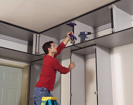 <b>Photo 13: Install the upper cabinets</b></br> <p>Set the upper cabinets on top of the lower cabinets and screw the uppers together with 1-1/4-in. screws. Then screw them to the wall studs and to the lower cabinets.</p>