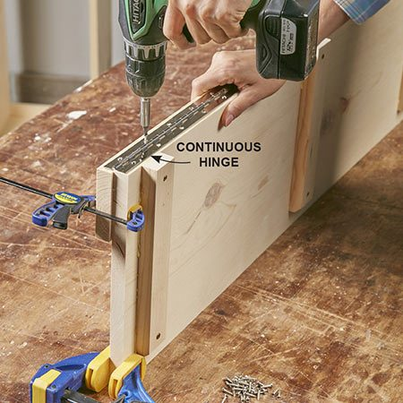 <b>Photo 6: Mount the seat hinge</b></br> <p>Clamp the lid and the back rail together as shown. Center the hinge on the two lid parts and attach it with four screws, two on each end. Then drill 5/64-in. pilot holes and drive in the remaining screws.</p>