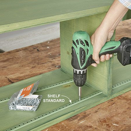 <b>Photo 7: Install the shelf standards</b></br> Cut each of the 72-in. shelf standards into two 34-3/4 in. pieces using a hacksaw. Measure from the ends to the centers to retain factory ends on each piece. We spray-painted the standards to match the finish.