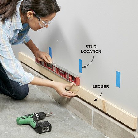 <b>Photo 8: Install temporary suppport</b></br> <p>Locate the wall studs with a stud finder and mark them with strips of masking tape. Install a 1x2 ledger with the top edge 7-1/2 in. above the floor to support the shelves and seat while you install them.</p>