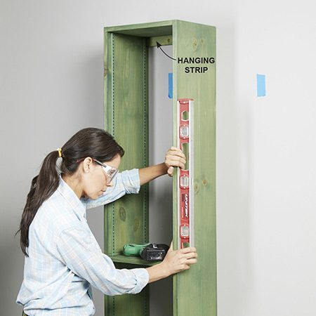 <b>Photo 9: Install the first shelf unit</b></br> <p>Rest the shelf on the ledger. Drive a screw through the top hanging strip into a stud. Then use a level to make sure the sides of the shelf unit are plumb. If necessary, push the bottom one way or the other to plumb the sides. Drive a screw through the lower hanging strip into a stud to secure the shelf unit.</p>