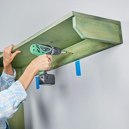 <b>Photo 10: Install the coat-hook shelf</b></br> <p>Screw the coat-hook shelf to the studs, making sure it's level. Then level the shelf from front to back and attach it to the side of the tall shelf with 1-1/4-in. screws. Attach the opposite side after you've installed the second shelf unit.</p>